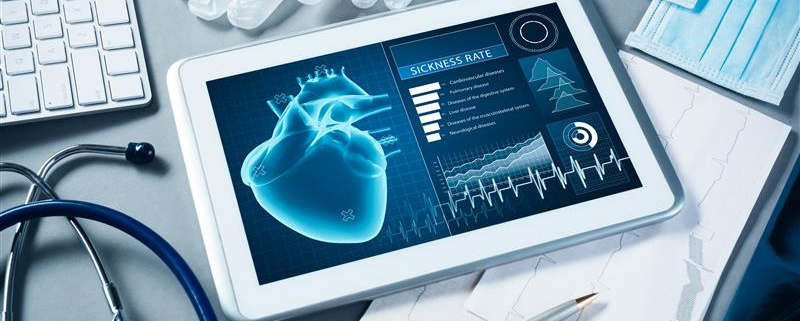 Tablet on messy desk with a virtual heart with vitals on the screen